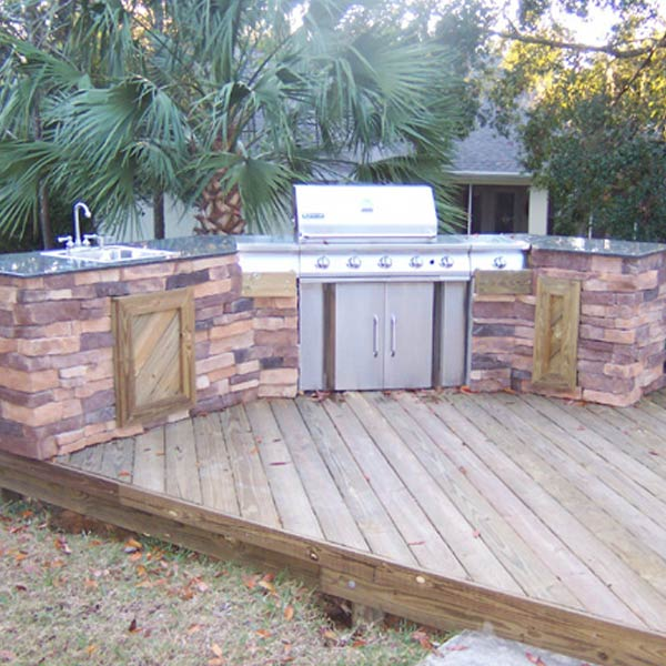 Enjoy cooking outdoors with a custom designed and built outdoor kitchen on your deck. The shape of this kitchen follows the lines of the existing deck and the same natural wood was used in the kitchen's details to tie the two structures together. The back has a variety of colors in it to add visual interest and texture.