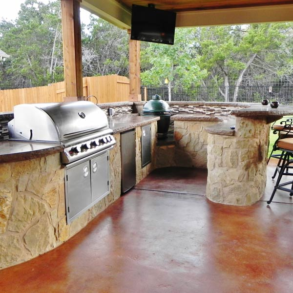 This well-equipped kitchen is designed and built for owners who enjoying entertaining outdoors. A curved design was used to provide flow while maximizing the prep space. The contrast between the natural stone and deep reds in the stamped concrete makes the outdoor kitchen pop on the space. The countertops are granite with rough edges for a more rustic look.