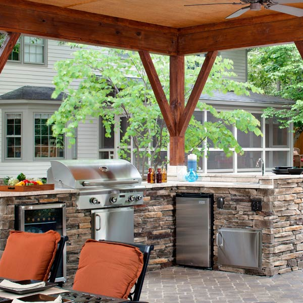 This open porch in North Carolina has plenty of space for cooking and dining. For the owners who love to entertain, Archadeck designed and built this custom kitchen with a built in grill, sink and two refrigerators, one for food and one for drinks. Natural stone was used on its base to complement the paver patio's grey tones.