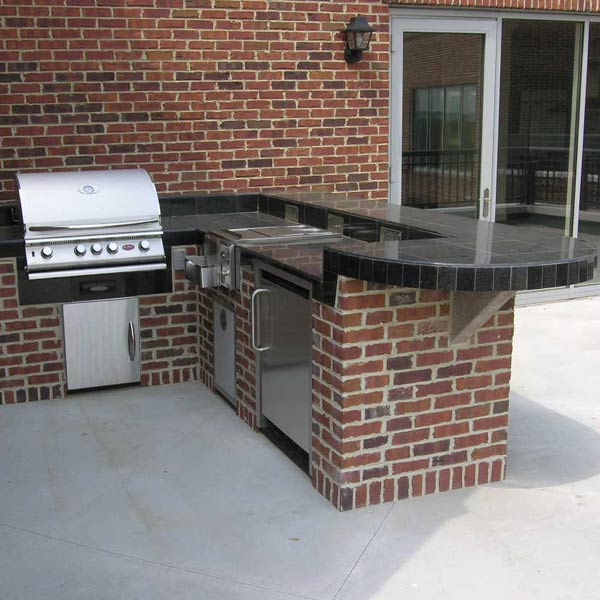 With a grill, refrigerator, and burners, this L-shaped outdoor kitchen is perfect for cooking outside. Brick was used on the base of the structure to match the brick on the existing home. The black tile countertop complements the home's black details.