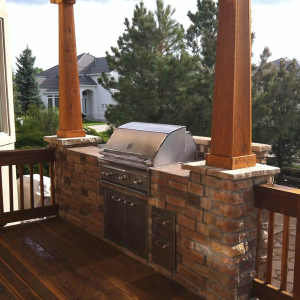 This custom designed and built outdoor kitchen was the finishing touch on its respective open porch. The porch's wooden columns sit atop the beautiful stone of the outdoor kitchen, marrying the two structures together. With space to prep and cook food, the kitchen has everything the owners need.