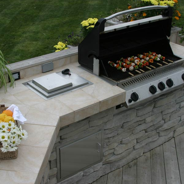 The light colored stacked stone and tile of this outdoor kitchen design perfectly complements the light wood deck. Additional wood details were added to the kitchen to further marry the two structures. With plenty of counter space and a large grill, this beautiful outdoor kitchen is the perfect place to grill dinner.