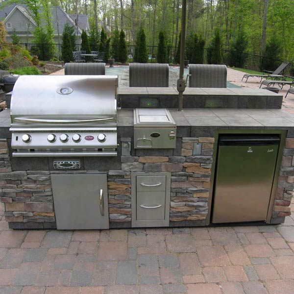 Overlooking the backyard's pool area, this custom outdoor kitchen was designed to keep people outside even longer on nice spring and summer days. Constructed using natural stone and tile, the kitchen includes a gas grill, warming tray and refrigerator. An umbrella stand was built into the kitchen to provide the chef and diners a place to escape the sun.