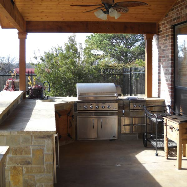 Designed with natural stone to complement the natural wood ceiling, this outdoor kitchen design was created with the homeowners' needs in mind. They needed something functional with counter space for food prep and serving along with the grill. The long counters offers plenty of room for everything they need.