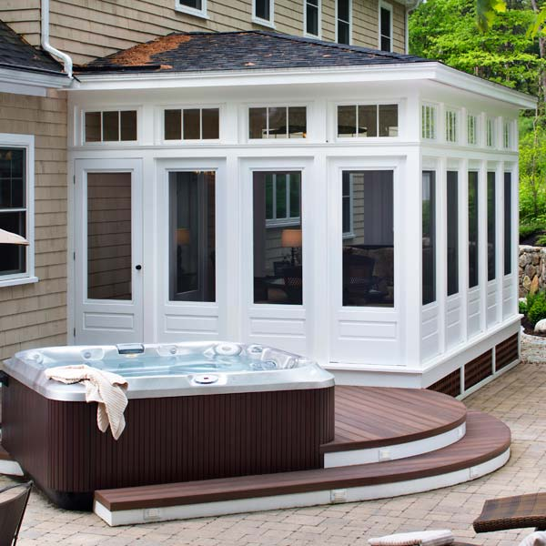 After lounging in their Archadeck sunroom, this family steps down and into the soothingly warm bubbling waters of this jacuzzi hot tub. The adjacent patio area accommodates an outdoor dining space as well as lounge chairs for further relaxation.